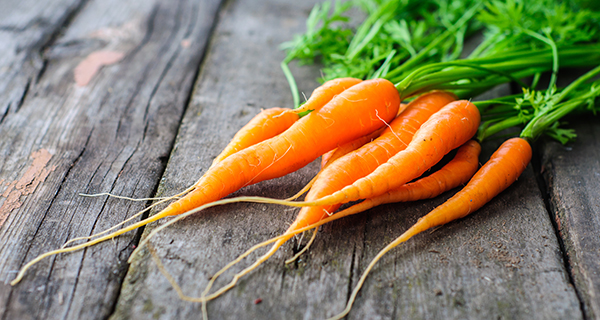 Bunch of fresh washed carrot on the old wooden background